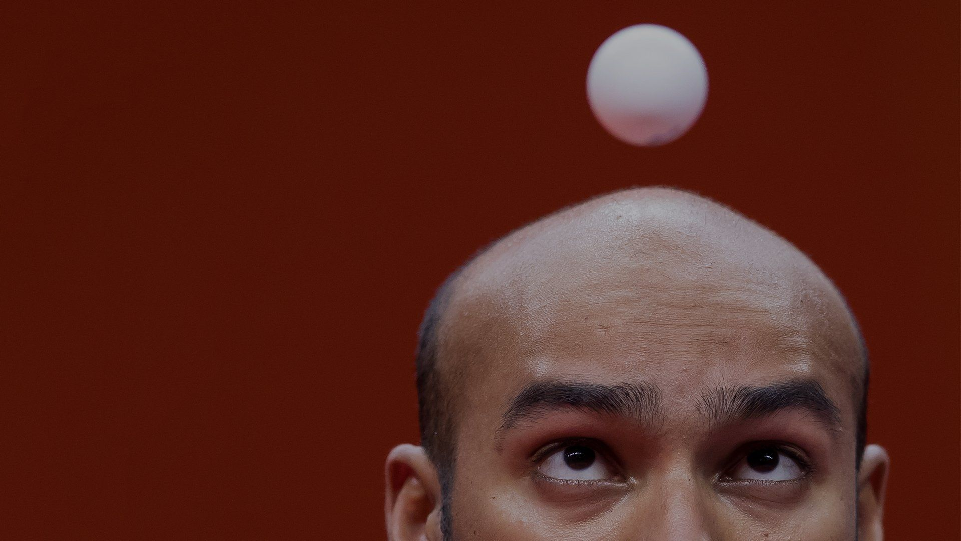 A close-up of table tennis player Rhikesh Taucoory with the ball appearing to hover just in front of his face. Photo by Mark Kolbe.